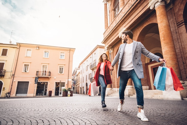 Joven pareja feliz con bolsas de compras en la ciudad Foto Premium