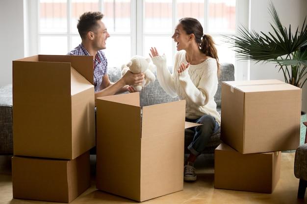 Joven pareja feliz divirtiéndose cajas de embalaje en nuevo hogar Foto gratis