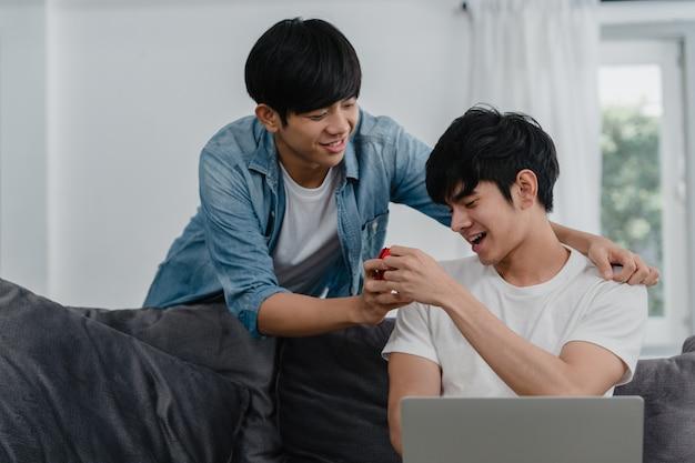 Joven pareja gay asiática propone en casa moderna, los hombres lgbtq coreanos adolescentes sonrientes felices tienen un momento romántico mientras proponen y el matrimonio sorpresa usa el anillo de bodas en la sala de estar de la casa. Foto gratis