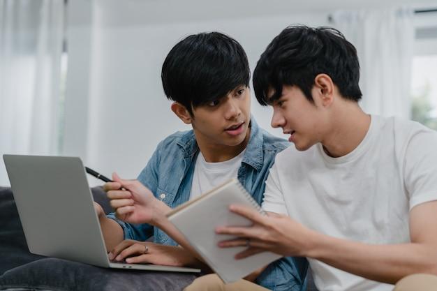 Joven pareja gay asiática trabajando portátil en casa moderna. asia lgbtq + hombres felices relajarse divertirse usando la computadora y analizar sus finanzas en internet juntos mientras se está acostado en el sofá de la sala de estar en casa. Foto gratis