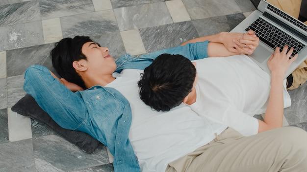 Joven pareja gay usando la computadora portátil en casa moderna. los hombres asiáticos lgbtq felices se relajan divertidos usando tecnología viendo películas en internet juntos mientras están acostados en el piso de la sala de estar en casa. Foto gratis