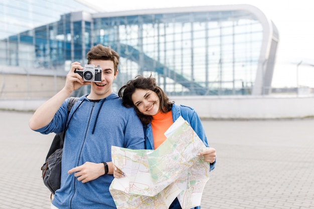 Joven pareja linda. niño y una niña caminando por la ciudad con un mapa y una cámara en sus manos. los jóvenes viajan. Foto Premium