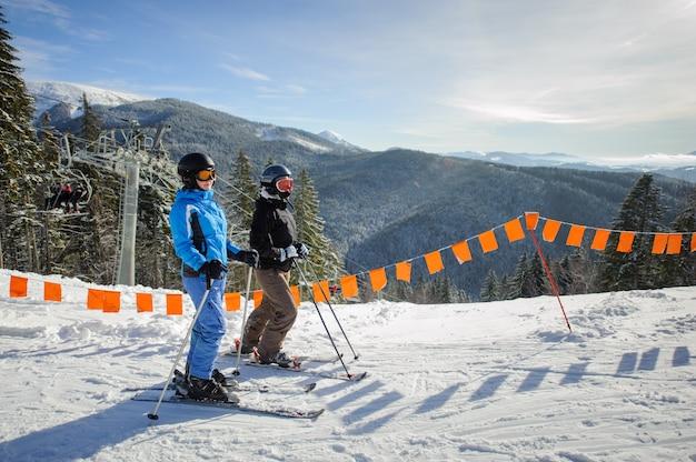Joven pareja de mujeres disfrutando del esquí en la estación de esquí Foto Premium