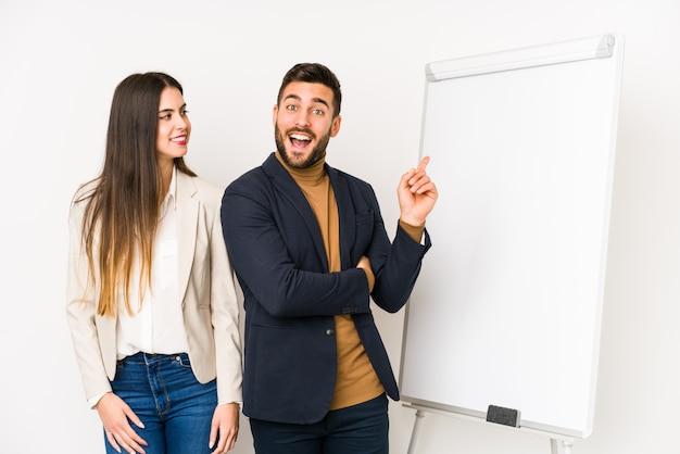 Joven pareja de negocios sonriendo alegremente señalando con el dedo lejos Foto Premium