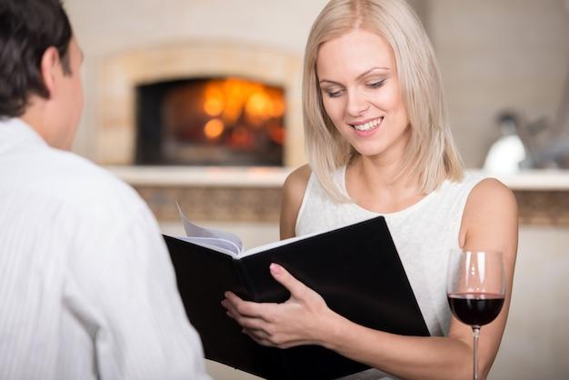 Joven pareja en restaurante animando con vino tinto. Foto Premium