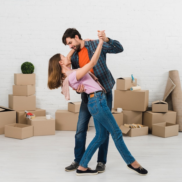 Joven pareja romántica bailando frente a cajas de cartón Foto gratis