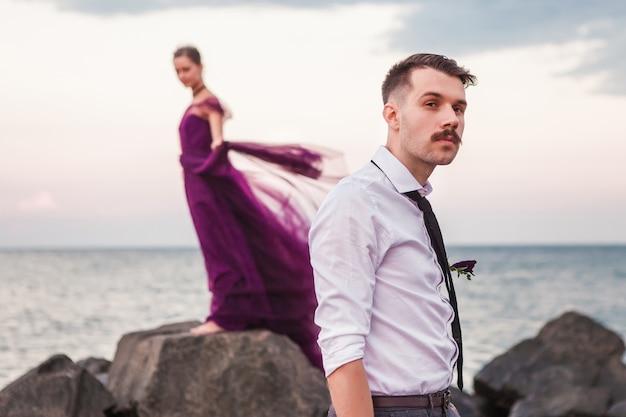 Joven pareja romántica relajante en la playa mirando el atardecer Foto gratis