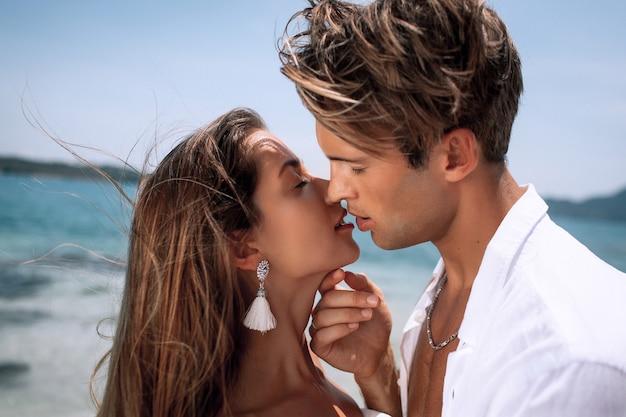 Joven pareja romántica en ropa blanca besándose en una playa tropical caliente. naturaleza luna de miel. phuket tailandia de cerca Foto Premium