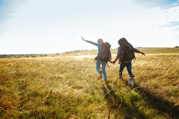 Joven pareja de viajeros caminando en campo con perro pug Foto gratis