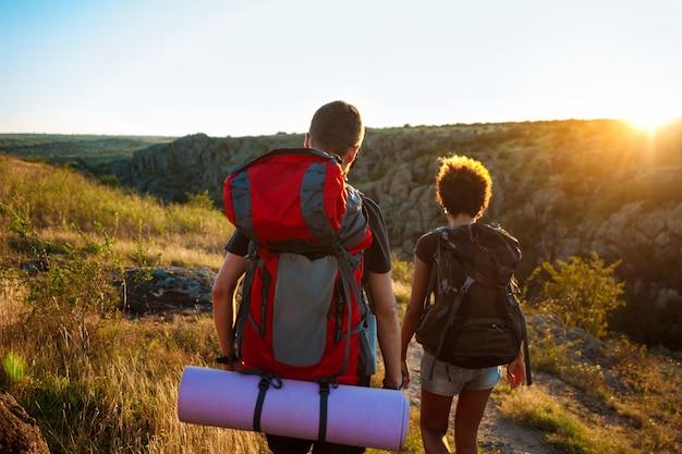 Joven pareja de viajeros con mochilas que viajan en el cañón al atardecer Foto gratis