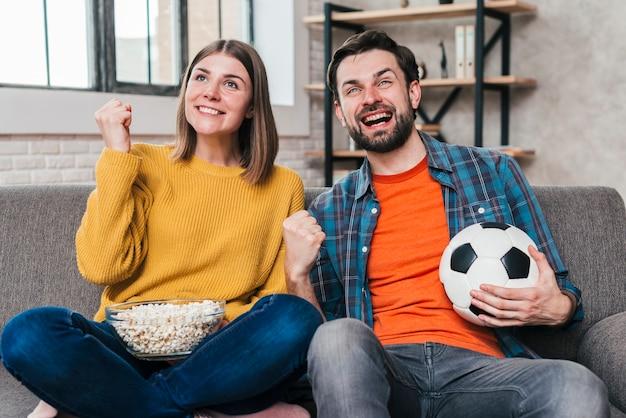 Joven pareja viendo el partido de fútbol animando después de ganar Foto gratis