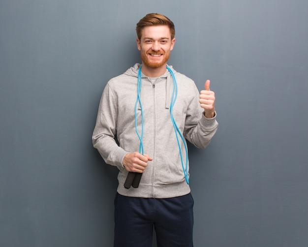Joven pelirroja fitness hombre sonriendo y levantando el pulgar Foto Premium