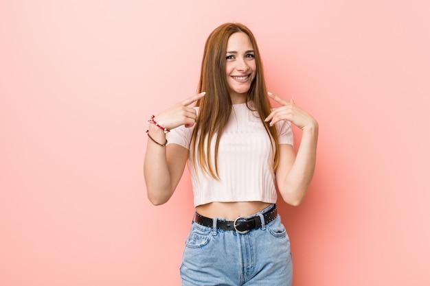 Joven pelirroja jengibre mujer contra una pared rosa sonríe, señalando con el dedo a la boca. Foto Premium