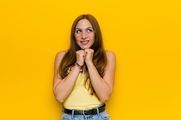 Joven pelirroja jengibre con pecosa mantiene las manos debajo de la barbilla, mira felizmente a un lado. Foto Premium