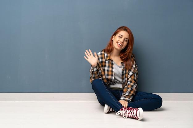 Joven pelirroja mujer sentada en el piso saludando con la mano con expresión feliz Foto Premium