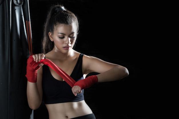 La joven está de pie, envuelta en un paño en las manos para practicar boxeo en el gimnasio. Foto Premium