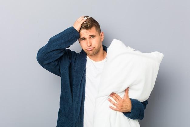 Joven con pijama sosteniendo una almohada sorprendida, ella ha recordado una reunión importante. Foto Premium