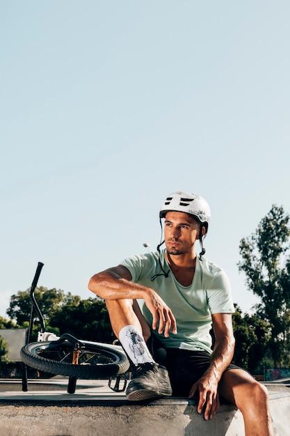 Joven piloto de bmx descansando en skatepark Foto gratis