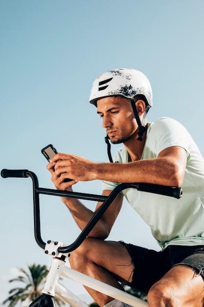 Joven piloto de bmx mirando el teléfono plano medio Foto gratis
