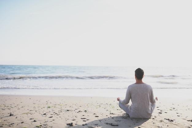 Joven practicar yoga en la playa al atardecer. Foto Premium