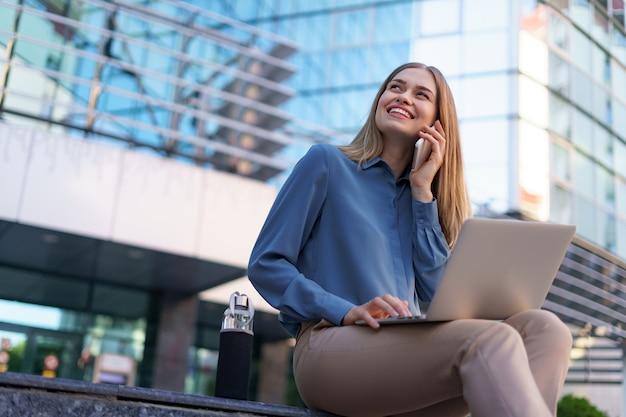 Joven profesional sentada en la escalera frente al edificio de cristal, sosteniendo el portátil en el regazo y hablando por teléfono móvil Foto gratis