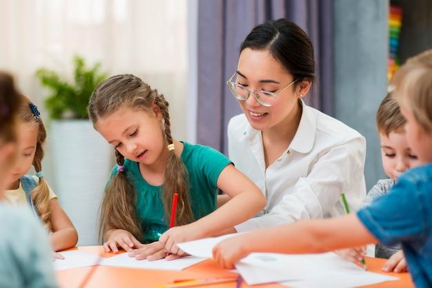 Joven profesora ayudando a sus alumnos en clase Foto gratis
