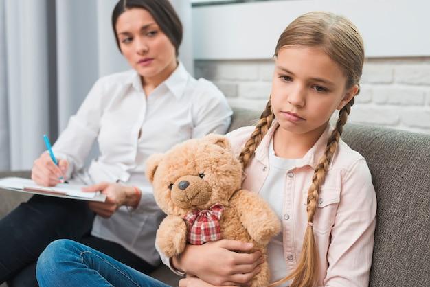 Joven psicóloga observando a la niña triste sentada con un oso de peluche. Foto gratis