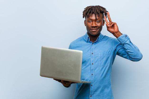 Joven rasta negro sosteniendo una computadora portátil que muestra el signo de la victoria y sonriendo ampliamente. Foto Premium