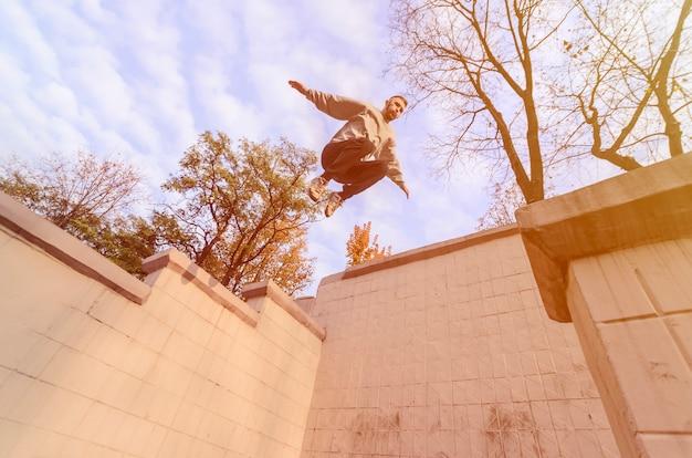 Un joven realiza un salto por el espacio entre edificios. Foto Premium
