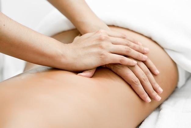 Joven recibiendo un masaje de espalda en un centro de spa. Foto gratis