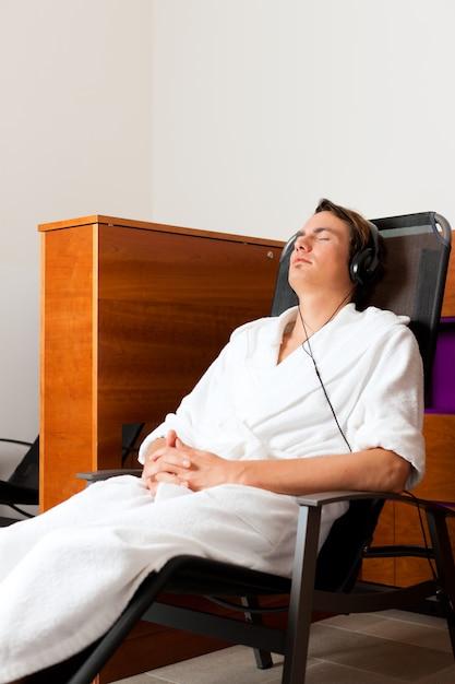 Joven relajante en el spa con música Foto Premium