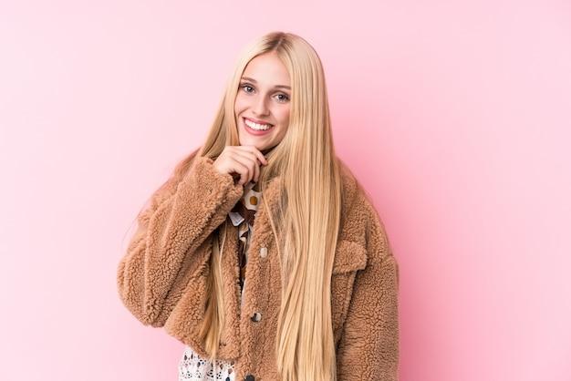 Joven rubia con un abrigo contra una pared de color rosa sonriendo feliz y confiado, tocando la barbilla con la mano. Foto Premium