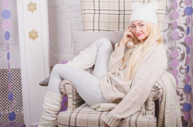 Joven rubia en un divertido sombrero sentado en una acogedora silla de navidad, emociones positivas y cálidas Foto Premium