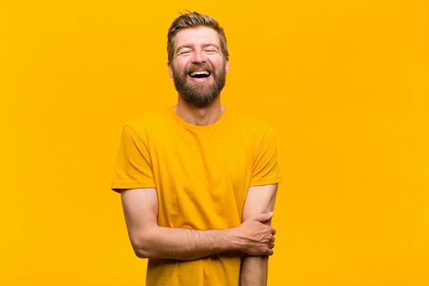 Joven rubia riendo con timidez y alegría, con una actitud amigable y positiva pero insegura Foto Premium