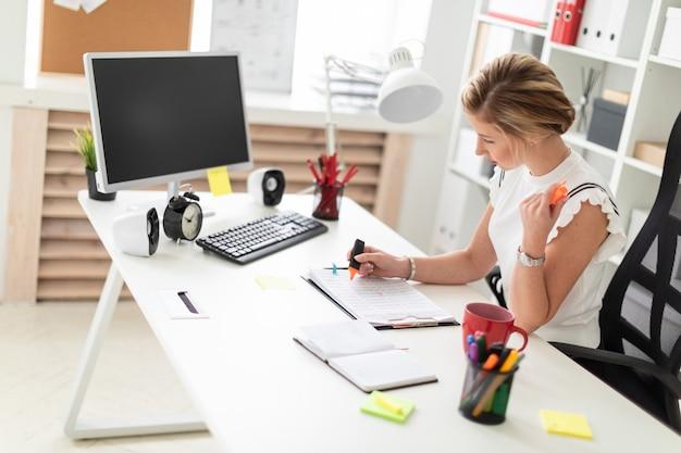 Una joven rubia se sienta en el escritorio de una computadora en la oficina, sostiene un marcador naranja en la mano y trabaja con documentos. Foto Premium