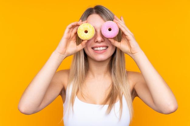 Joven rubia sobre pared aislada con donas en los ojos Foto Premium
