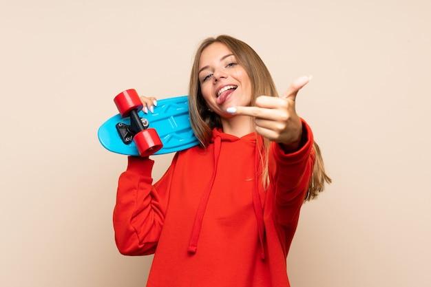Joven rubia sobre pared aislada con skate Foto Premium