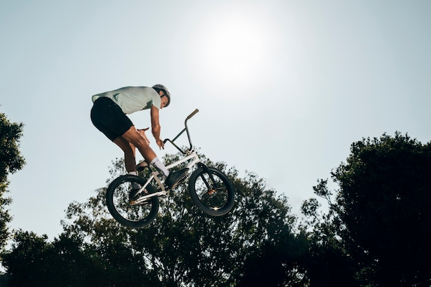Joven saltando con bicicleta arriba Foto gratis