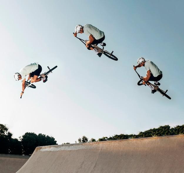 Joven saltando con bicicleta bmx en el skate park Foto gratis