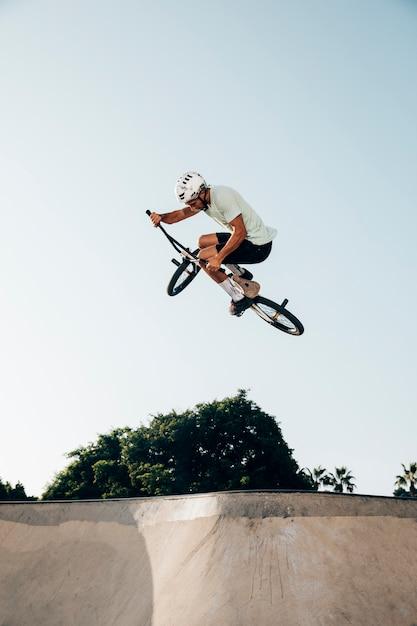 Joven saltando con bicicleta bmx Foto gratis