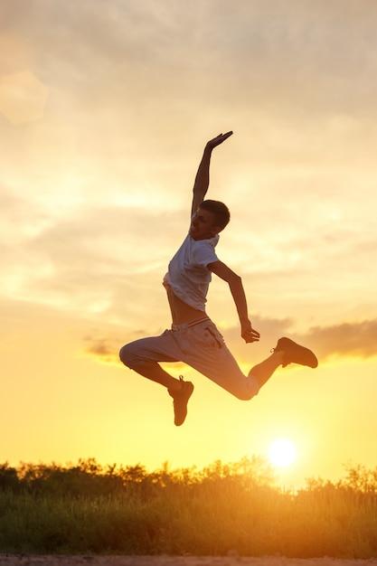 Joven saltando contra el cielo del atardecer Foto Premium