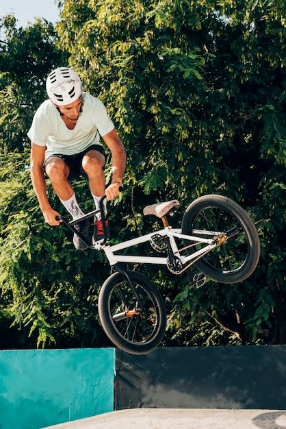 Joven saltando con tiro largo de bicicleta bmx Foto gratis