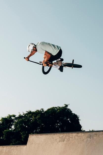 Joven saltando con vista de ángulo bajo de bicicleta bmx Foto gratis