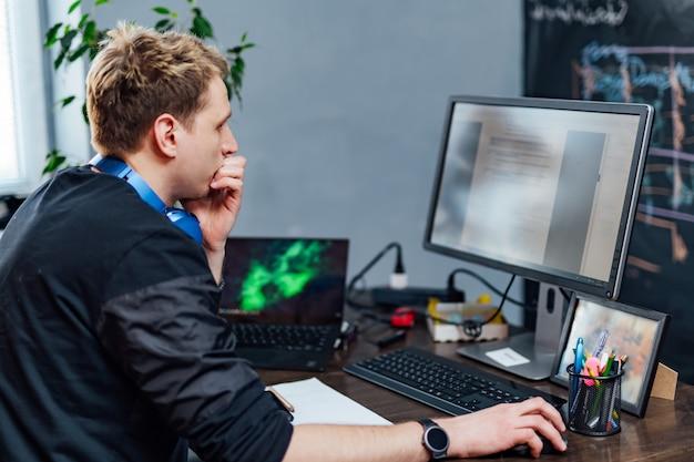 Joven serio se concentró en el problema en la pantalla de la pc. el programador inteligente está trabajando duro en su empresa en interiores. Foto Premium