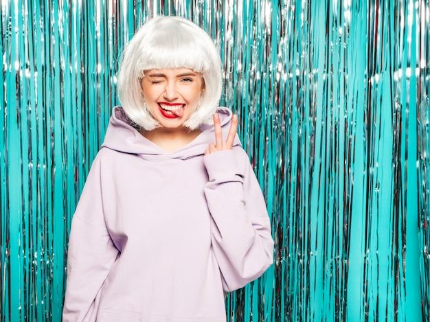 Joven sexy chica hipster sonriente en peluca blanca y labios rojos. hermosa mujer de moda en ropa de verano. Foto gratis