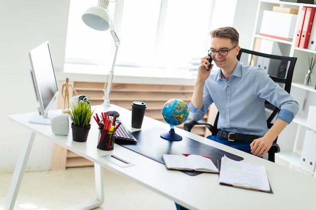 Un joven se sienta en la oficina en el escritorio de una computadora, hablando por teléfono y mirando el globo. Foto Premium