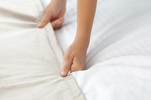 Joven sirvienta haciendo cama en la habitación del hotel Foto Premium