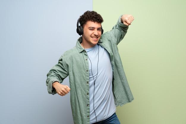Joven sobre azul y verde escuchando música con auriculares y bailando Foto Premium
