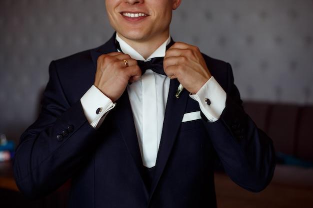 Joven sonriente en camisa blanca y traje negro ajusta la mariposa de cerca. chico elegante pone un traje de negocios. novios mañana cerca Foto Premium