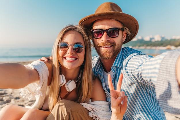 Joven sonriente feliz hombre y mujer en gafas de sol sentado en la playa de arena tomando fotos selfie en la cámara del teléfono Foto gratis